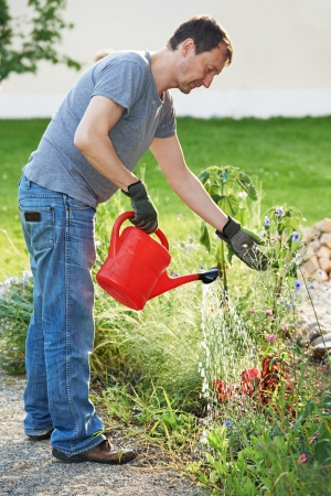 watering pot: man pouring water at garden with watering can