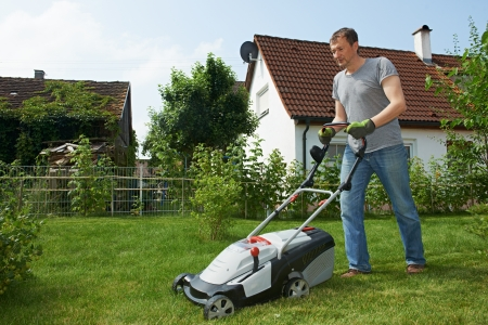 lawn mowing: man cutting grass in his garden yard with lawn mower