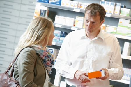 cheerful pharmacist chemist man worker standing at pharmacy drugstore desk with colleague photo