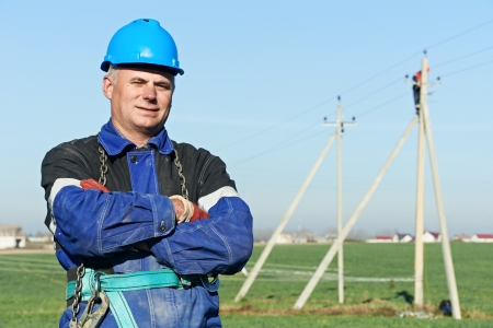 Portrait of power line repairman electrician worker on electric post pole work photo
