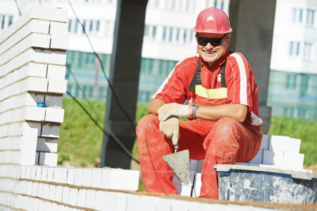 Portrait of Builder construction mason worker bricklayer with trowel putty knife outdoors photo
