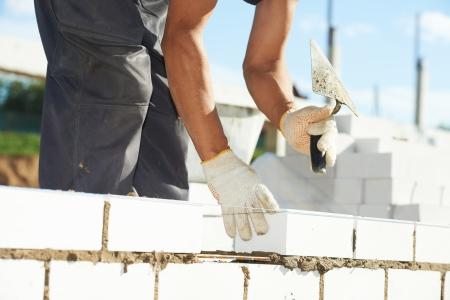 煉瓦こてパテのナイフを屋外でインストール プロセスの石大工工事のクローズ アップ 写真素材