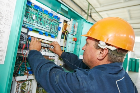 service panel: electrician at work checking wire with drawing inspecting high voltage power electric line distribution fuseboard Stock Photo