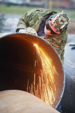 Construction Welder worker in protective glasses cutting metal pipe at building site with welding flame torch cutter photo