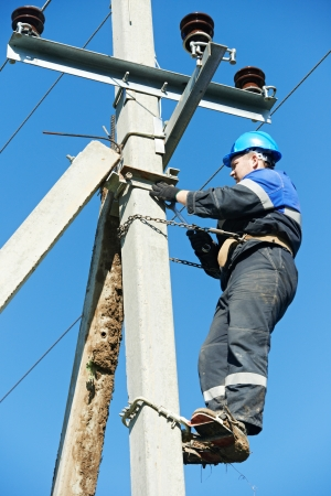 Electrician lineman repairman worker at climbing work on electric post power pole photo