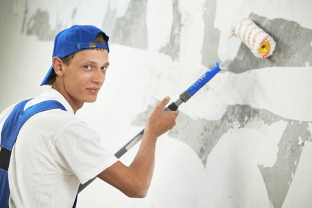One painter with paint roller making wall prime coating  at home repair renovation work Stock Photo