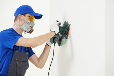refit: Home improvement worker in protective mask and glasses working with sander for smoothing wall surface