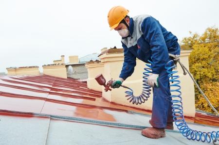 Conciatetti costruttore lavoratore con polverizzatore spruzzatura vernice sul tetto di lamiera Archivio Fotografico - 22801815