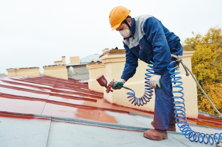 coating: roofer builder worker with pulverizer spraying paint on metal sheet roof