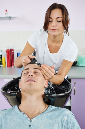 Washing man client hair in beauty parlour hairdressing salon photo