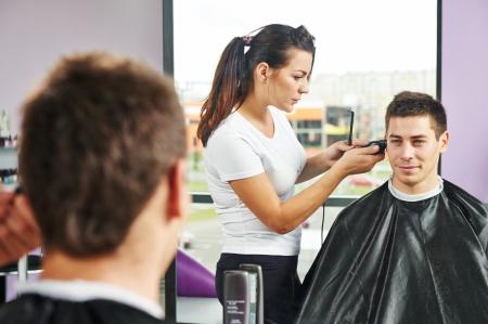 резка: Женский парикмахер резки волосы улыбающийся человек клиента в салоне красоты