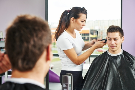 dresser: Female hairdresser cutting hair of smiling man client at beauty parlour
