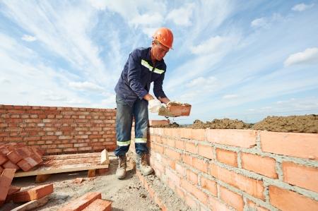 야외 흙 퍼티 나이프와 붉은 벽돌을 설치 건설 메이슨 작업자 벽돌공