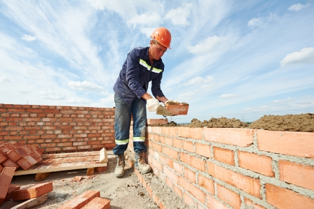 plastering: construction mason worker bricklayer installing red brick with trowel putty knife outdoors Stock Photo