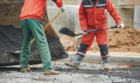 asphalting: builders workers at asphalting paver machine during Road street repairing works