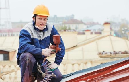 steeplejack: roofer builder worker with pulverizer spraying paint on metal sheet roof
