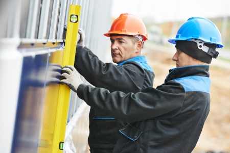 Stukadoor bouwer werknemer met niveau onderzoekt metalen profiel gevel plaat installatie