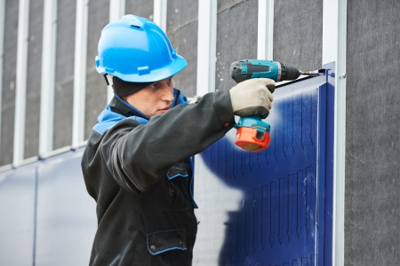screwing: construction worker with screwdriver installing facade metal profile plate