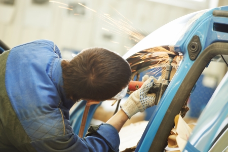 automobile industry: professional repairman worker in automotive industry grinding metal body car with sparks