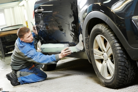 damage control: repairman worker in automotive industry stopping car body before painting or repaint at auto repair shop