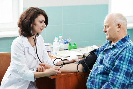 doctor nurse measuring blood pressure of patient by phonendoscope in clinic hospital photo