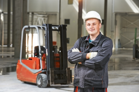 young smiling warehouse worker driver in uniform in front of forklift stacker loader