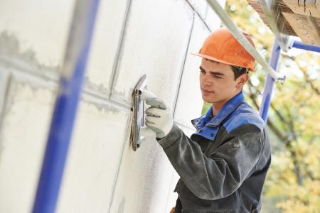 sandpaper: builder worker facade building with sandpaper Stock Photo