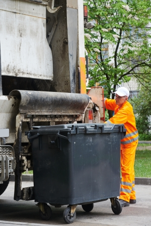 Worker of recycling garbage collector truck loading waste and trash bin photo