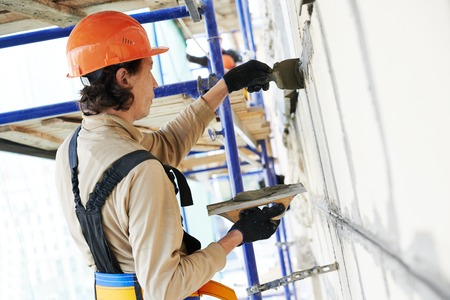 steeplejack: builder worker works with facade joint of building with plaster and spatula