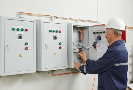 building maintenance: senior adult electrician builder engineer testing equipment in fuse box Stock Photo
