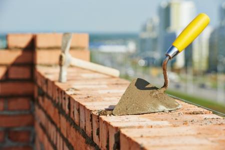 paredes de ladrillos: herramientas de trabajo albañil de construcción. Paleta de ladrillo y recoger martillo al aire libre en el área de construcción