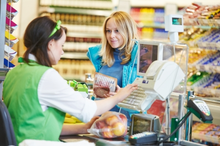 saleswomen: Customer buying food at supermarket and making check out with cashdesk worker in store Stock Photo