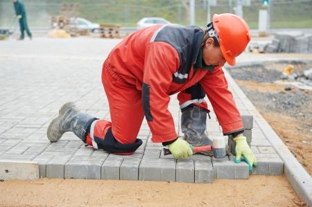 footway: mason worker making sidewalk pavement with stone blocks