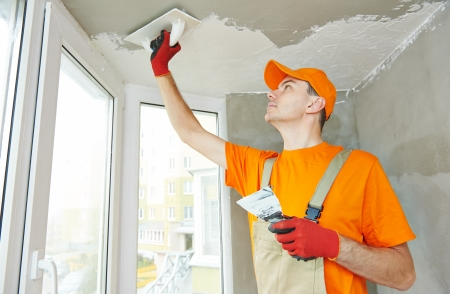 Plasterer at indoor ceiling renovation decoration with float and plaster