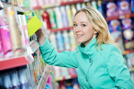 toiletry: woman choosing household chemistry produces in shopping mall