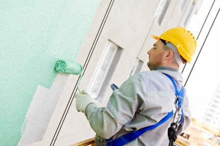 building industry: builder worker painting facade of high-rise building with roller