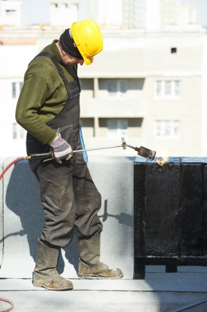 ruberoid: Roofer installing Roofing felt with heating and melting roll of bitumen roll by torch on flame