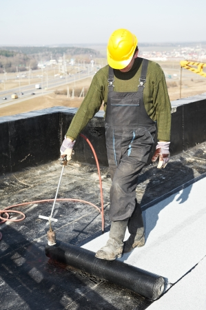 tar felt: Roofer installing Roofing felt with heating and melting roll of bitumen roll by torch on flame