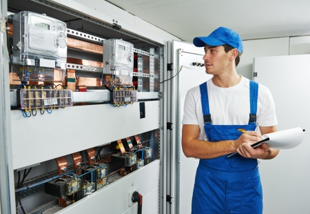 Young adult electrician builder engineer inspecting electric counter equipment in distribution fuse box photo