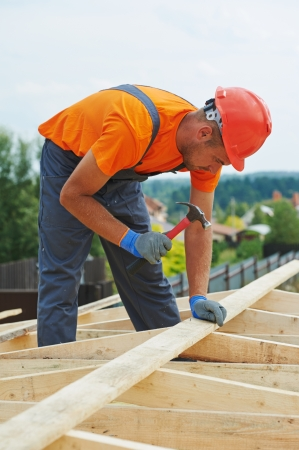 timber frame: construction carpenter worker nailing wood board with hammer on roof installation work Stock Photo