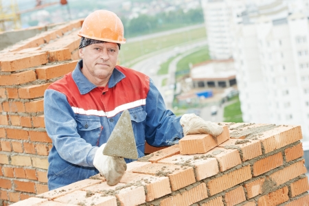 construction mason worker bricklayer installing red brick with trowel putty knife outdoors photo