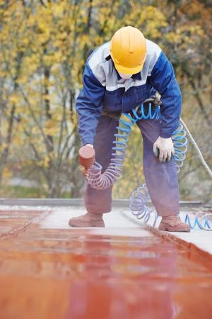 dakdekker bouwer werknemer met verstuiver spuiten verf op metalen plaat dak