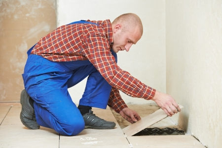 professional tiler builder worker installing home floor tile at repair renovation work photo