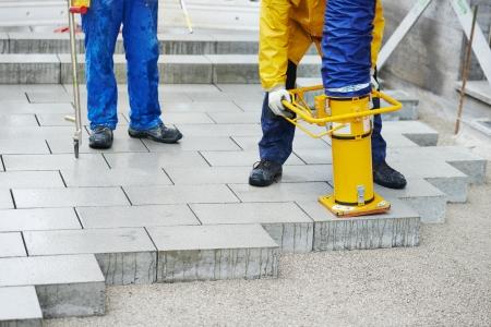 parapet: mason worker making sidewalk pavement with stone blocks