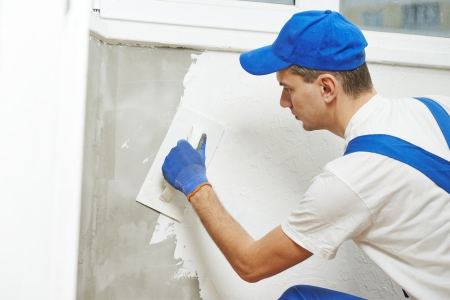plaster: Plasterer at indoor wall renovation decoration with float and plaster Stock Photo