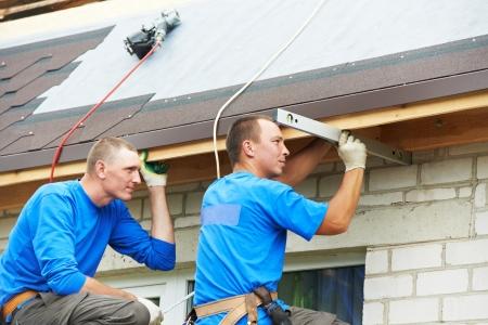 Montage: Arbeiter am Dach im Werk mit Flexfliesenmaterial Montage Dach Lizenzfreie Bilder