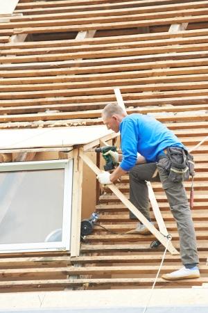 trussing: Operaio sul tetto a opere con piastrelle di materiale flex smontaggio coperture