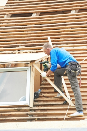 trussing: worker on roof at works with flex tile material demounting roofing Stock Photo
