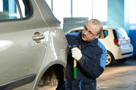 homme réparation automobile travailleur aplatir et aligner voiture de corps de métal avec un marteau dans l'industrie automobile