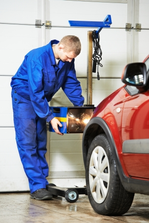 scheduled replacement: car mechanic inspecting headlight checkup automobile at repair service station Stock Photo